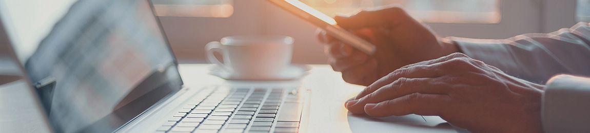Kuvassa: Kädet tietokoneen näppäimistöllä. Taustalla valonkajo.