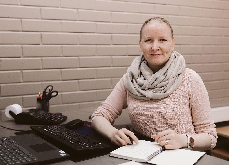Kuvassa Meeli Jürisson istuu toimistopöydän äärellä ja hymyilee.