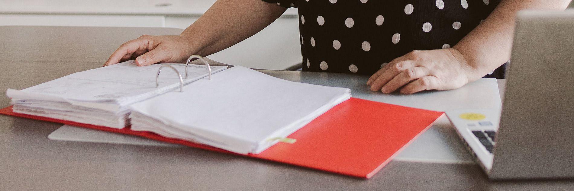 Kuvassa on etualalla auki punainen muistio, jonka takana on naisen kädet. Vierellä on kannettava tietokone.