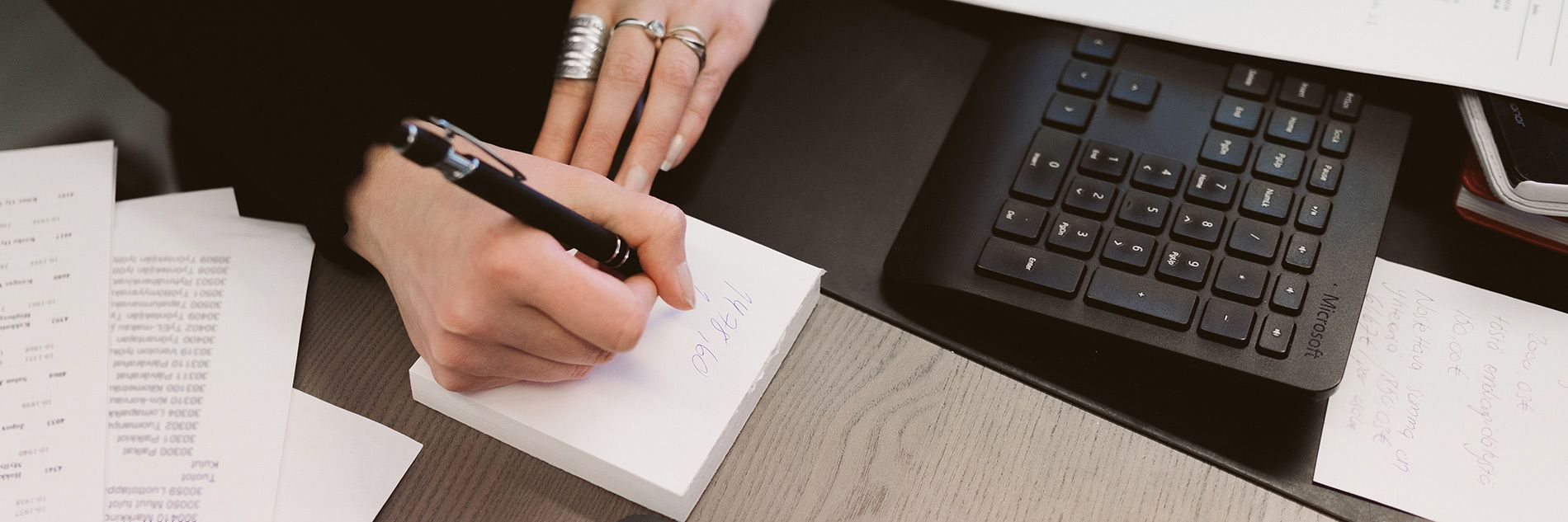 Kuvassa on kädet. Oikeassa kädessä on kynä, jolla kirjoitetaan muistiinpanoja. Käsien vieressä on tietokoneen näppäimistö.