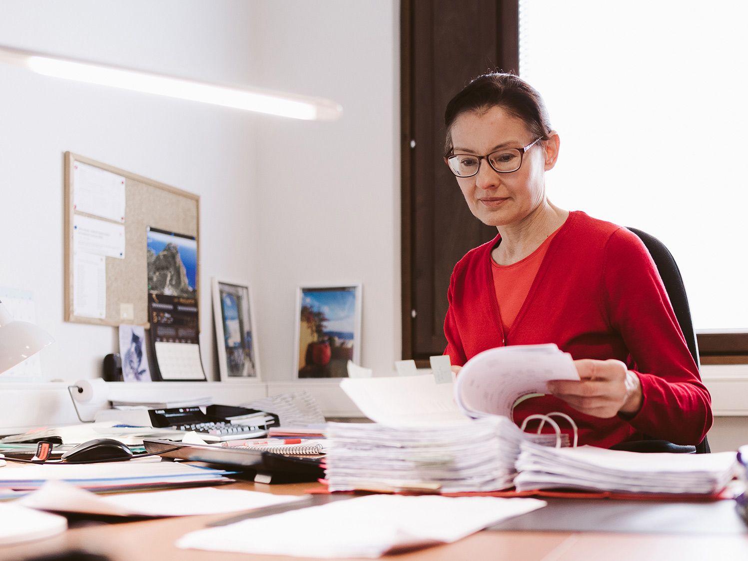 Kuvassa: Pirkko Villman istuu toimiston pöydän äärellä ja kääntää muistion sivua.