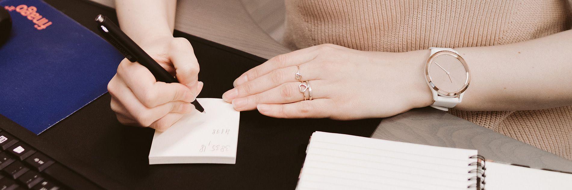 Kuvassa on kädet, joista oikea käsi kirjoittaa muistiinpanoja paperille.
