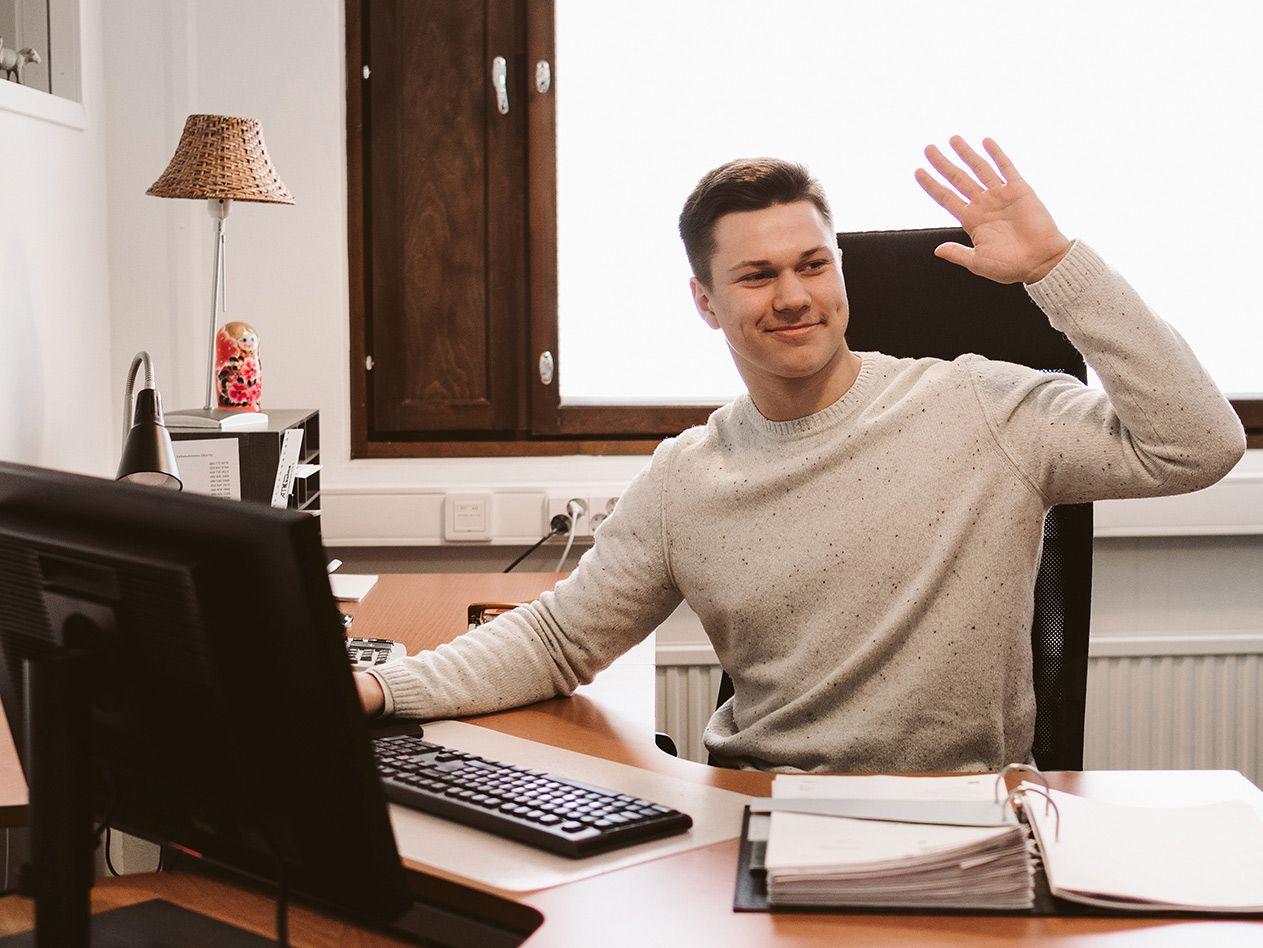 Kuvassa: Jaakko Suominen on toimistopöydän äärellä ja vilkuttaa oikealle päin.