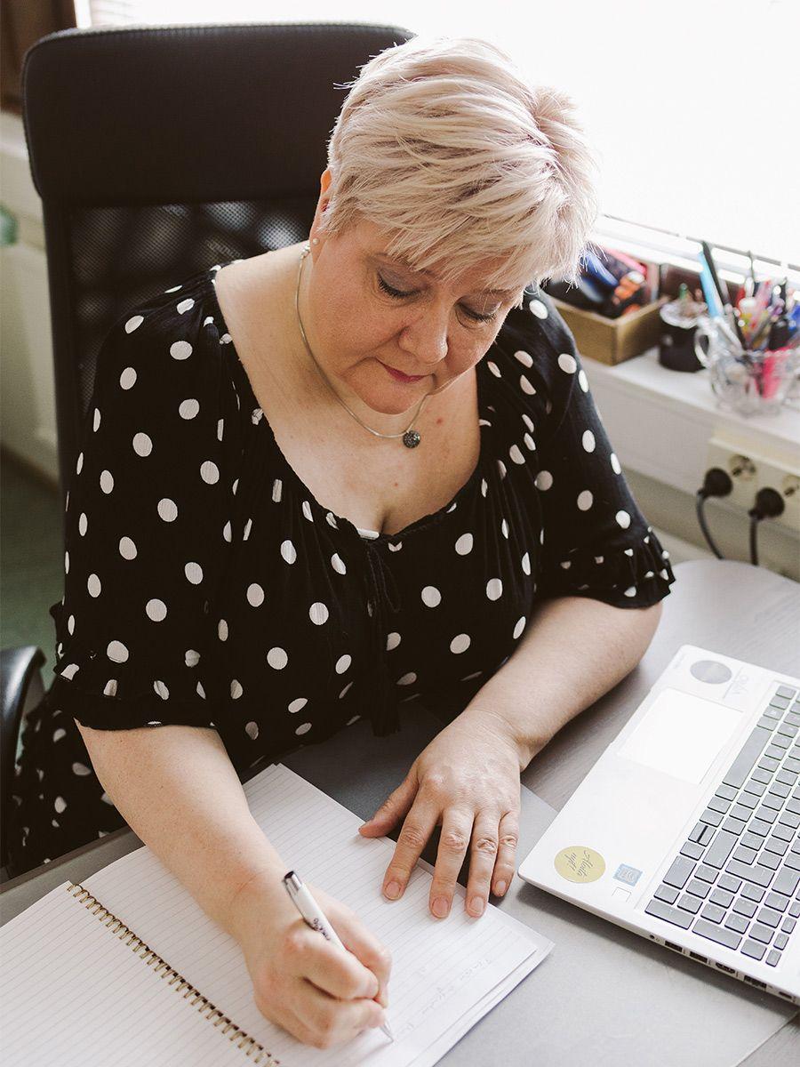 Kuvassa: Riikka Laakio kirjoittaa tietokoneen äärellä muistiinpanoja paperille.