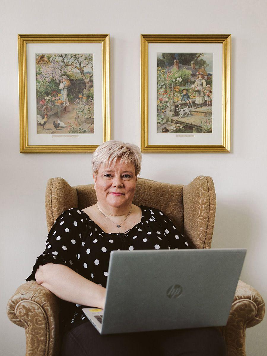 Kuvassa: Riikka Laakio istuu nojatuolissa sylissään kannettava tietokone.