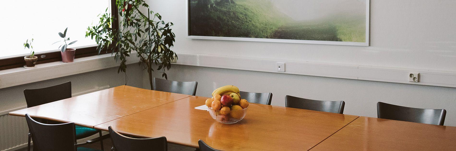 Kuva toimistosta, jonka keskellä on neuvottelupöytä. Pöydällä on hedelmiä.